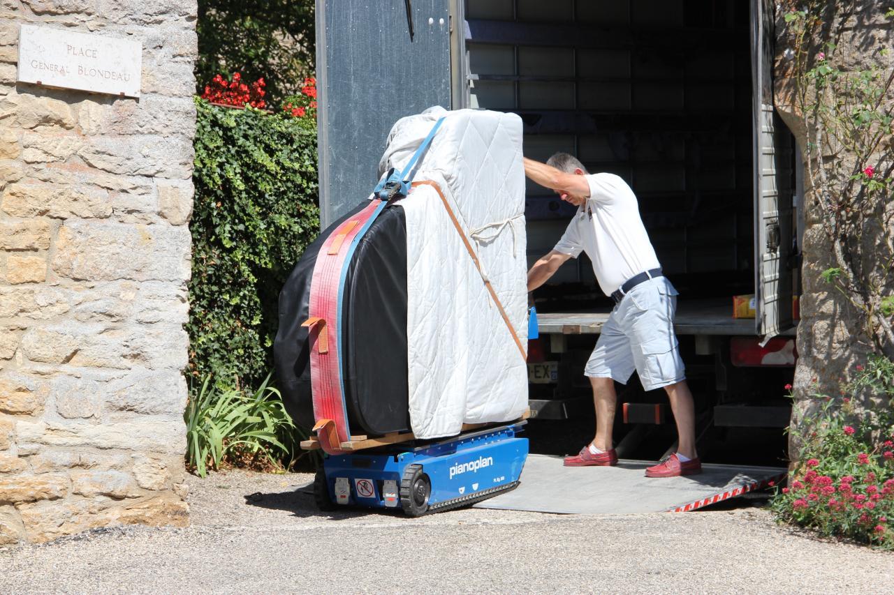 L'arrivée du piano. Bruno Prevalet pilote le petit robot transporteur